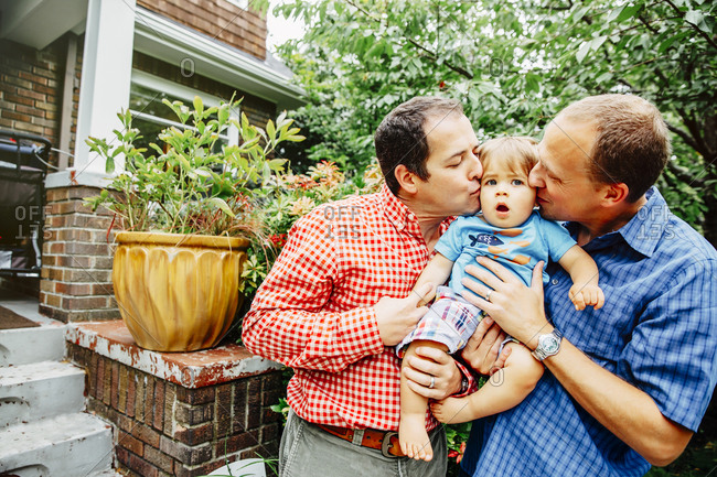 Gay fathers kissing baby son outdoors