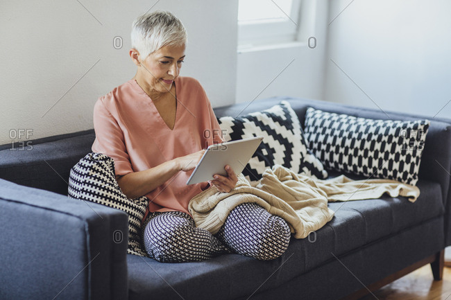Older Caucasian woman using digital tablet on sofa