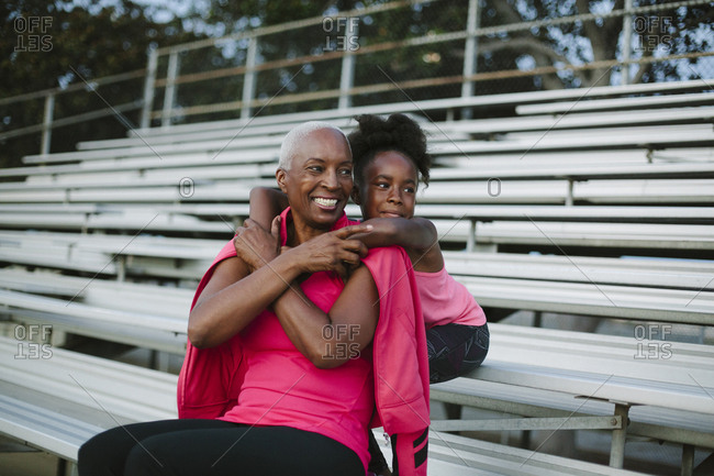 Grandmother and granddaughter sitting on bleachers