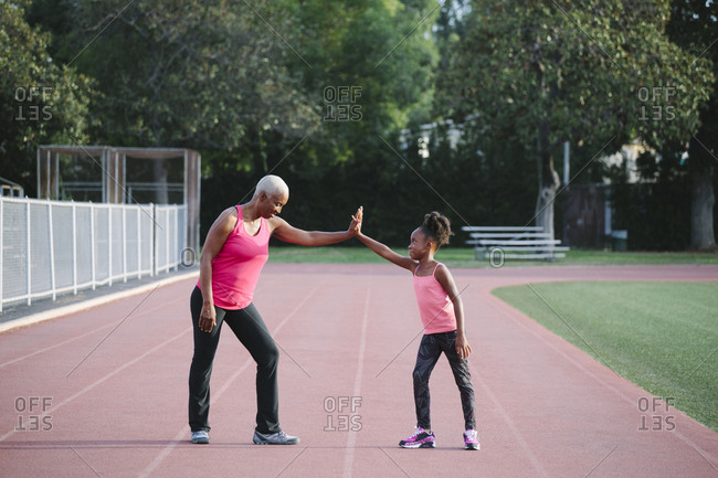 Grandmother and granddaughter high-fiving on track