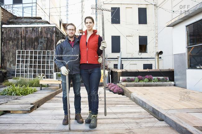 Couple holding rakes in urban rooftop garden