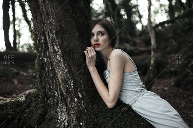 Caucasian woman leaning on tree in forest