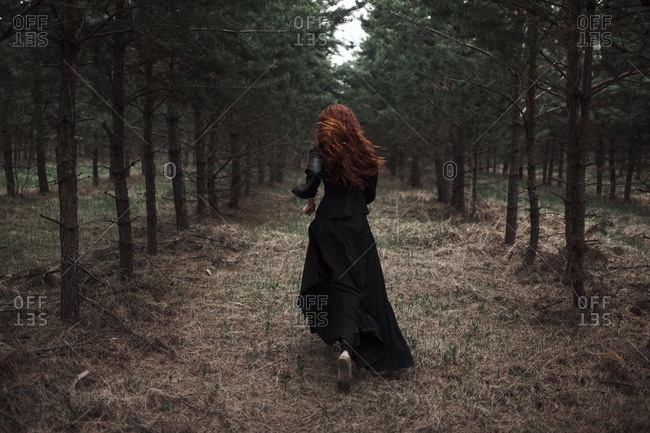 Caucasian woman walking on forest path