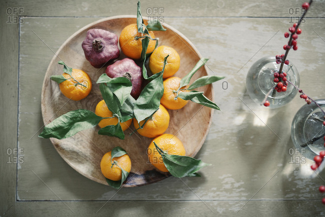 A wooden bowl of oranges, citrus fruits on a table top.