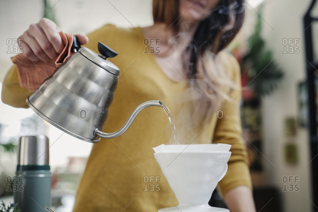 A woman pouring coffee from a pot through a paper filter.