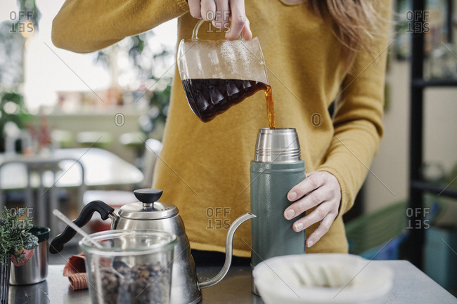A woman pouring coffee into a flask.