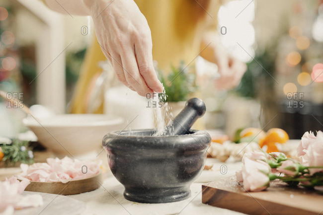 A hand adding ingredients to a pestle and mortar on a kitchen counter.