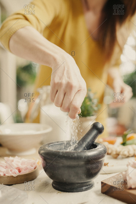 A woman adding ingredients to a pestle and mortar.
