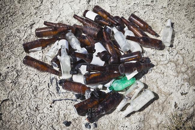 Discarded beer bottles in desert, close up