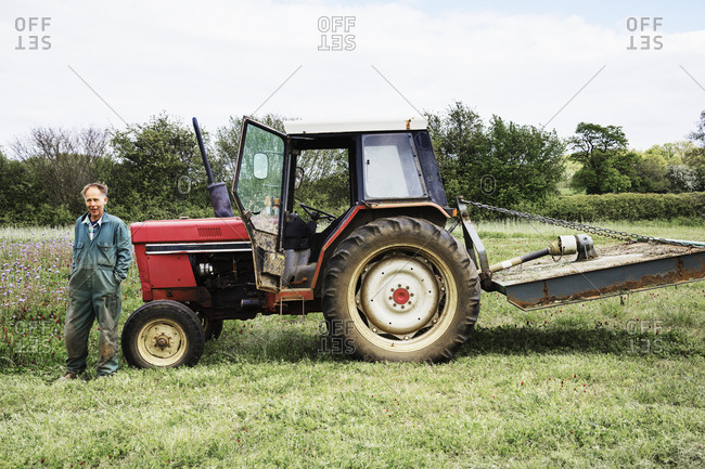 A stationary red tractor, and driver leaning against the bonnet, in a field in summer.