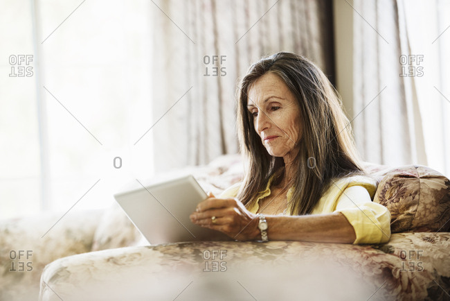 Senior woman with long brown hair sitting on a sofa, using a digital tablet.