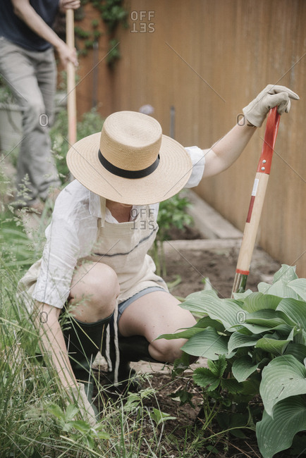 A woman in a wide brimmed straw hat working in a garden, digging.