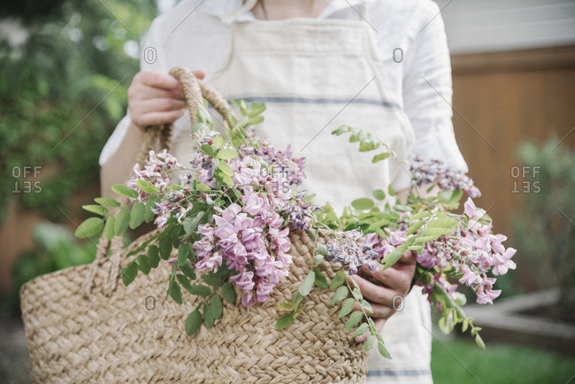 A woman holding a basket of cut branches with pink flowers.