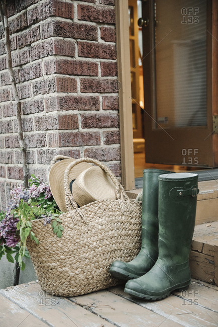 Wellingtons, rubber boots, basket and straw hat by a doorway.