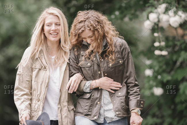 Two women walking arm in arm in the countryside.