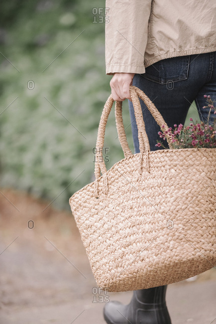 A woman carrying a wicker basket with flowers.