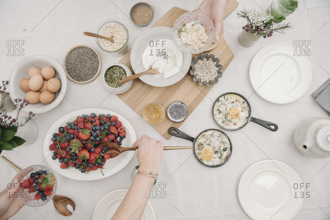 Overhead view of a table with food in dishes.  Breakfast, berries and yoghurt, eggs and bread.