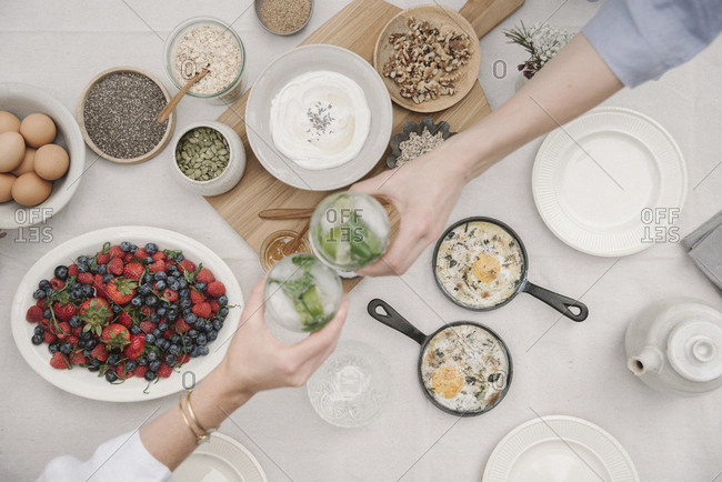 Overhead view of dishes of fruit, berries and yoghurt, eggs and cooked omelets