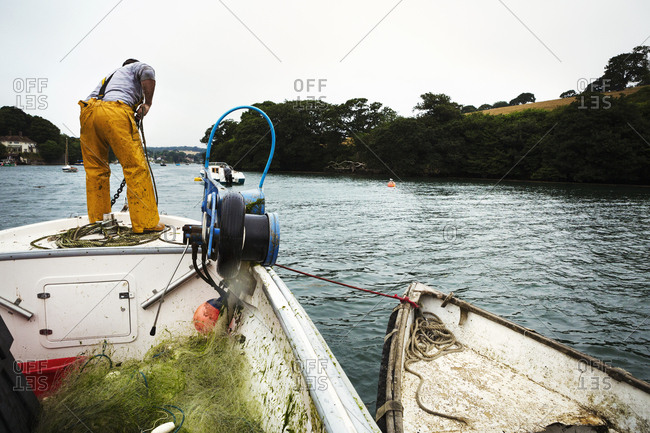 A fisherman in waders on a boat, hauling up the anchor.