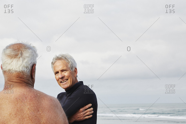 Two senior men standing on a beach chatting, one wearing a wetsuit.