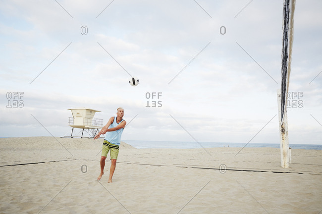 Mature man standing on a beach, playing beach volleyball.