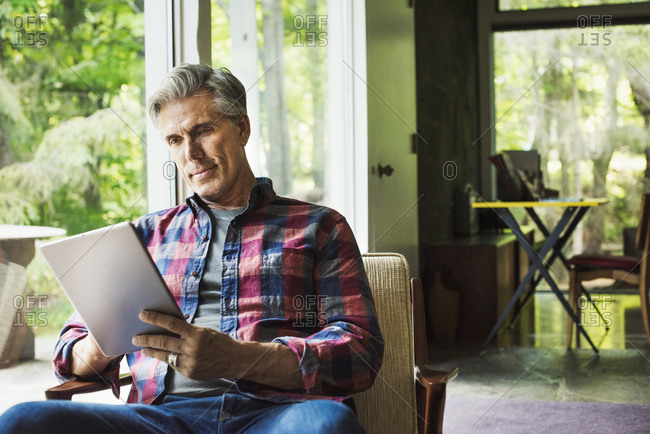 A man seated by a window reading using a digital tablet.