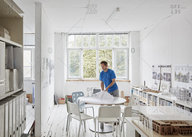 A man looking at plans at a table, architectural drawings. Building models on shelves.