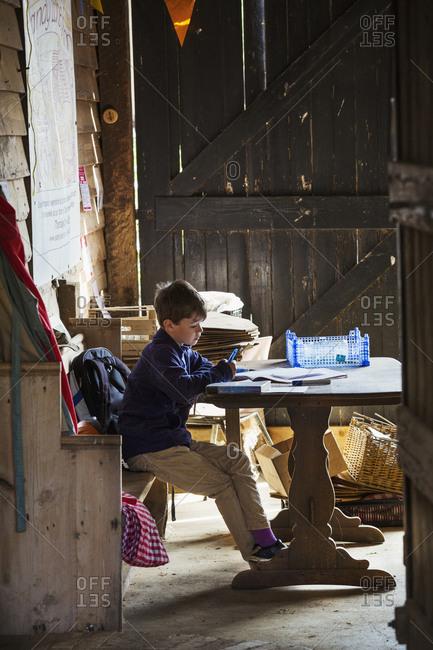 A child seated in a barn at a table doing his homework.