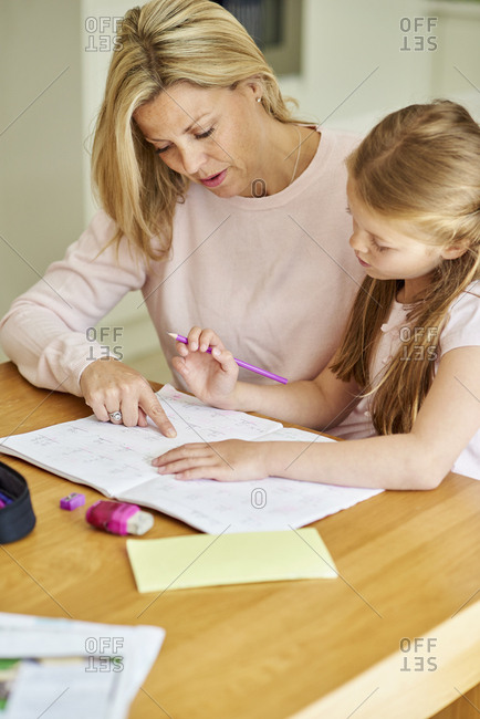 A woman and her daughter seated at a table checking her homework.