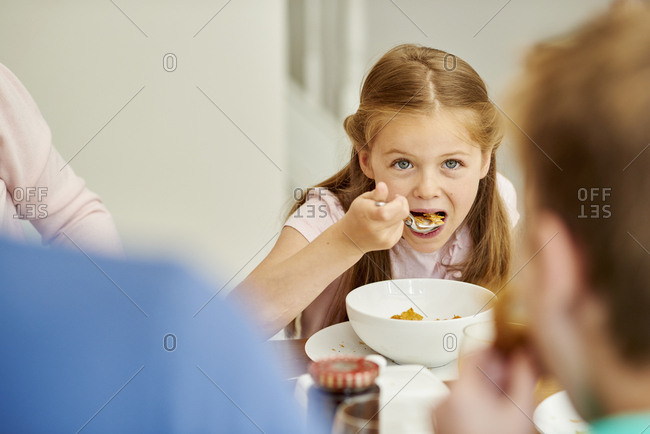 A family eating breakfast. A girl eating cereal with a spoon.