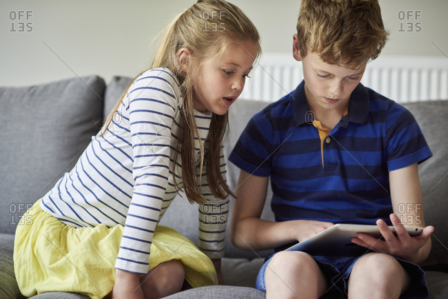 Two children seated sharing a digital tablet watching the screen.