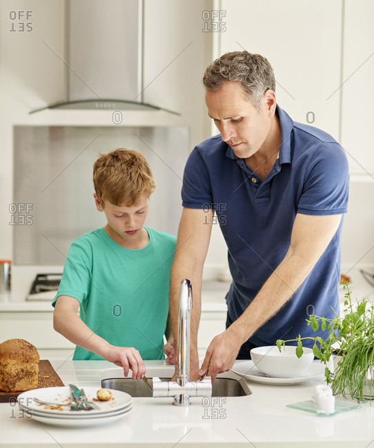 A family home. A man and a young boy in the kitchen side by side doing the dishes.