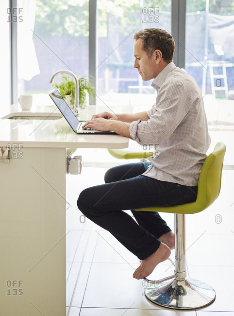A man seated on a kitchen chair at a counter, using a laptop computer.