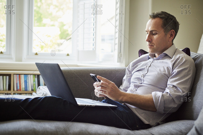 A man seated on a sofa at home using a laptop.