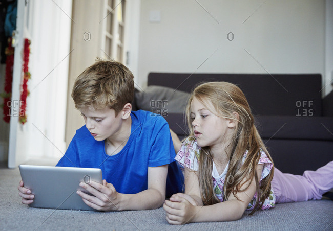 Two children lying on their stomachs sharing a digital tablet watching the screen.