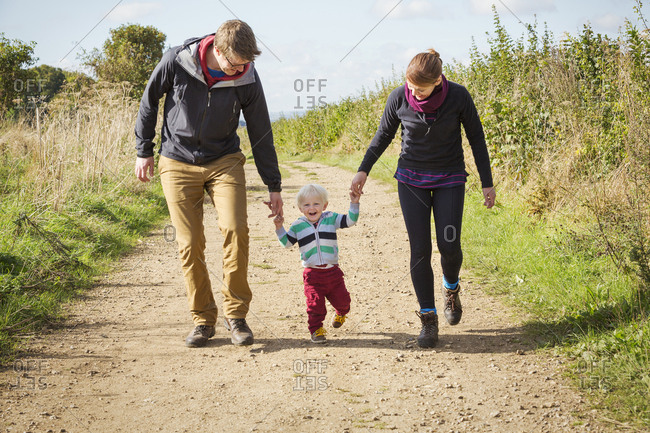 Parents and a child walking along a footpath in the countryside.