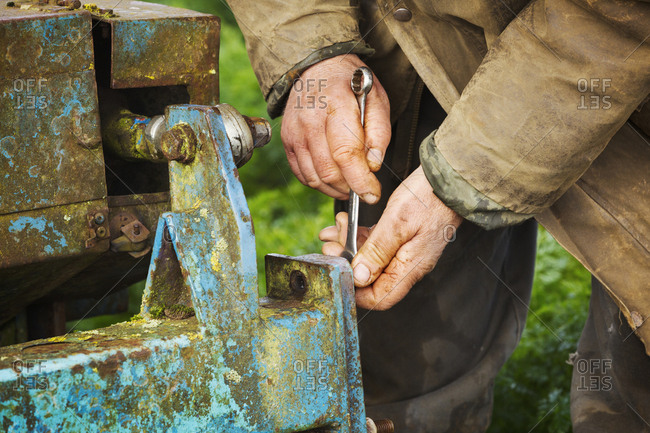 A man using a spanner on farm machinery, running repairs.