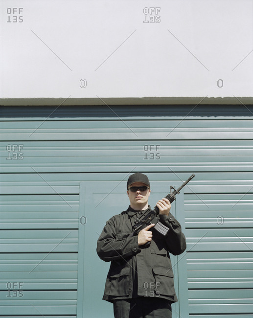 Man wearing special forces uniform and holding high powered semi-automatic rifle