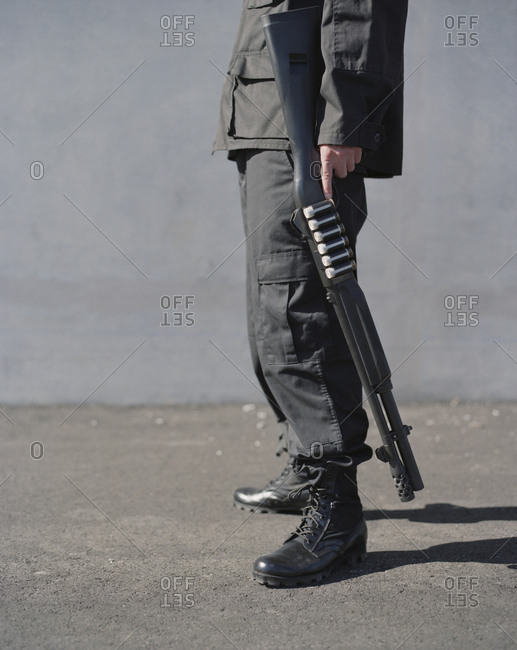Cropped view of man in special forces, holding high powered shotgun