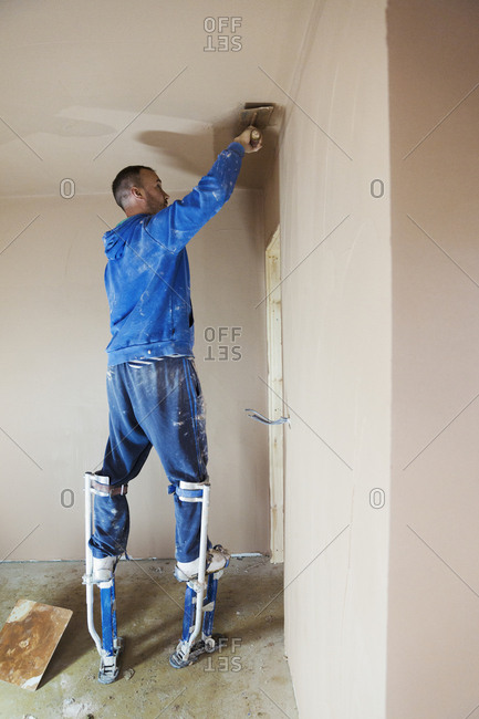 A plasterer wearing stilts smoothing fresh plaster high up on the walls of a house under construction.