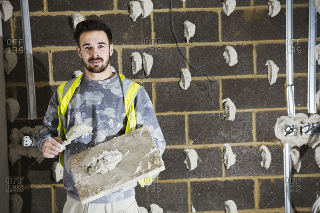 A plasterer, a builder with plasterboard and spreading trowel in front of a cinder block wall.