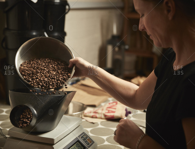 A coffee shop. A person pouring roasted coffee beans into a coffee grinder.