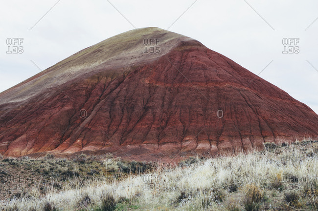The landscape of the John Day Fossil Beds National Monument, Oregon. Vivid colored rocks, the flanks of stone, folded and colored red.