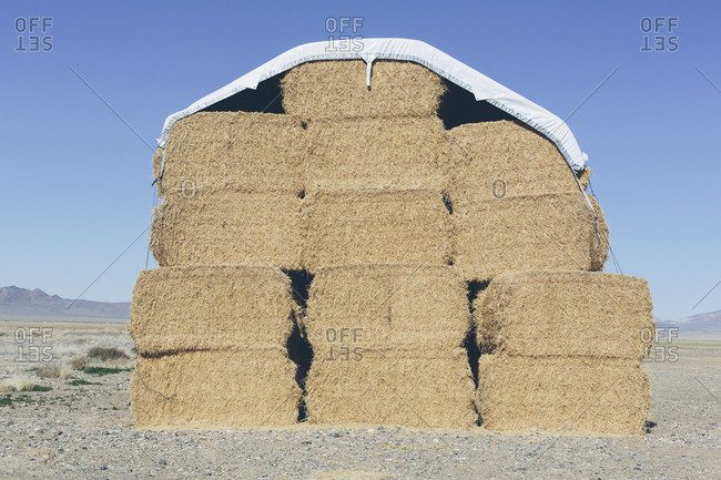 Tarpaulin covering stacked hay bales.