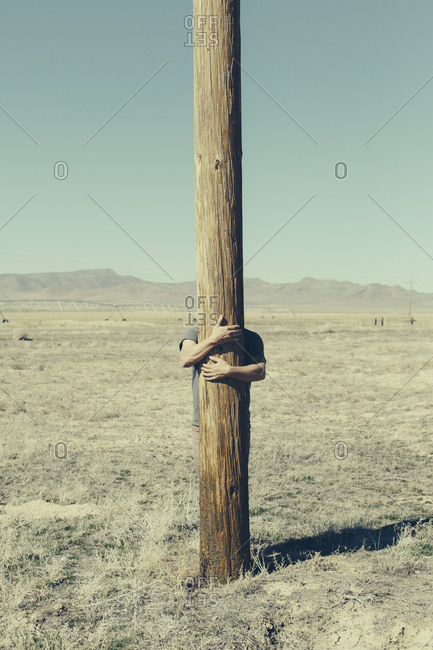 Man with his arms around a wooden utliities pole, clinging to or hugging the post in a flat open landscape.