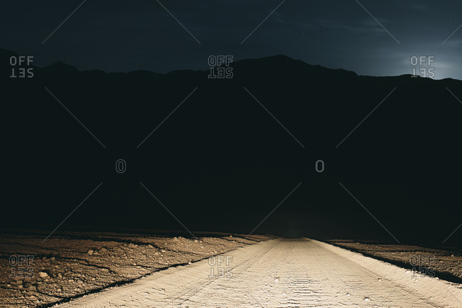 Dirt road in desert illuminated by car headlights, Death Valley National Park, USA, with moonlight in distance.