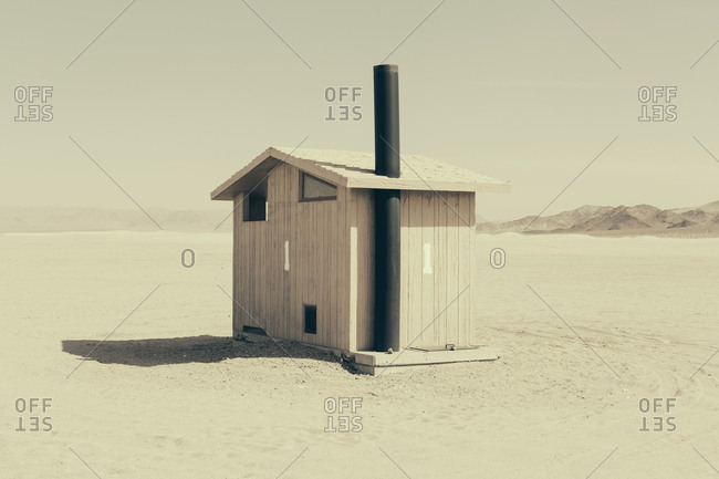 Restroom in an open space, a desert landscape. White sand and a small cabin building.