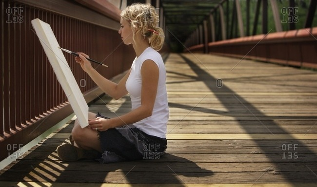 Young Artist Painting On A Bridge