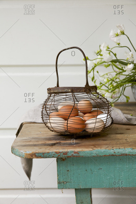 Eggs in a wire basket on rustic wooden table
