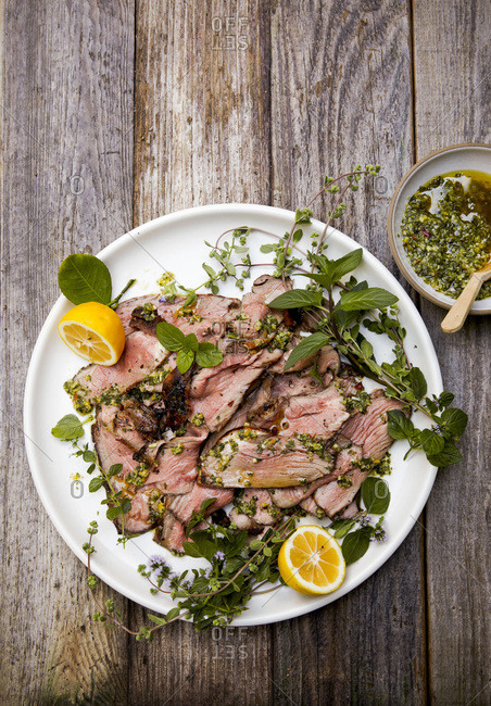 Plate of roast lamb with pesto and lemons on outdoor table